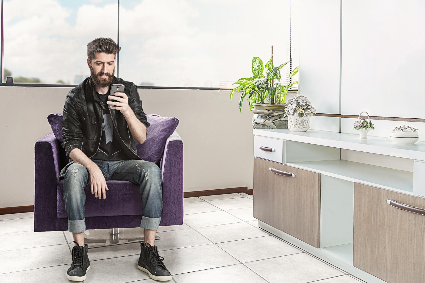 Rapaz usando smartphone sentado em uma poltrona